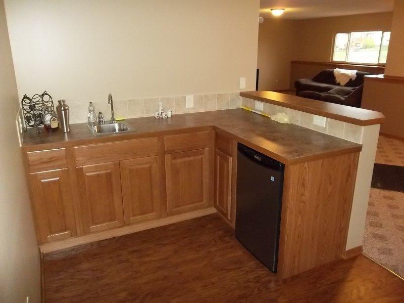 With Oak Cabinets And Laminate Countertop. Bar Refrigerator Under Cabinet  And Tile Backsplash.